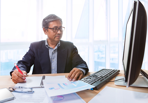 senior business man working on office table with paper report on table